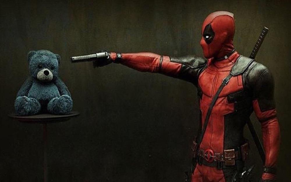 Still of Deadpool pointing a gun at a teddy movie wallpaper