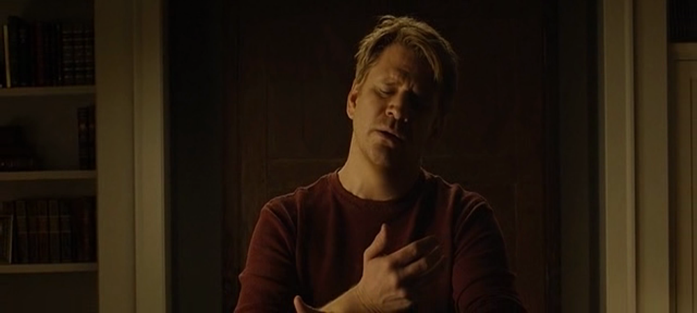 still of dash mihok as whelan holding her invisible wife in his hands