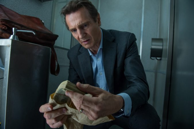 Liam Neeson handling wads of cash in The Commuter